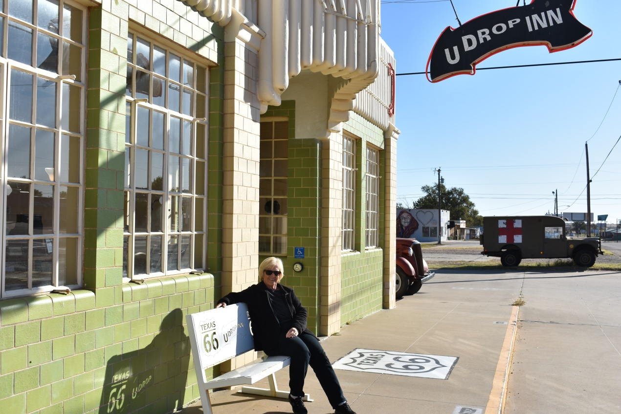 Judy sitting on the bench in front of the U Drop Inn Café in Shamrock Texas